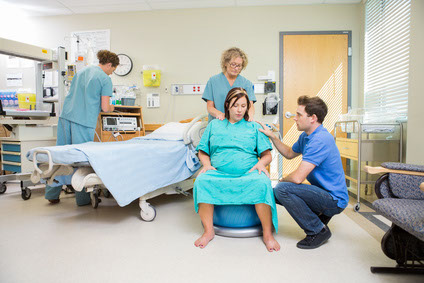 Photo of  a female in labour in a hospital room, partner giving support